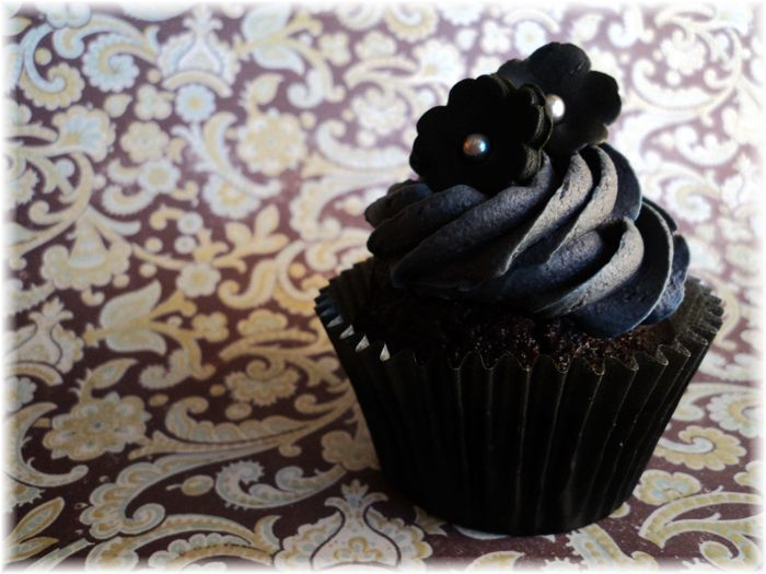 """Devil's chocolate cake with coloured vanilla buttercream and black dark chocolate fondant hand-made flowers."" Created by cupcake artisan, Sarah-Lyn Amaral."