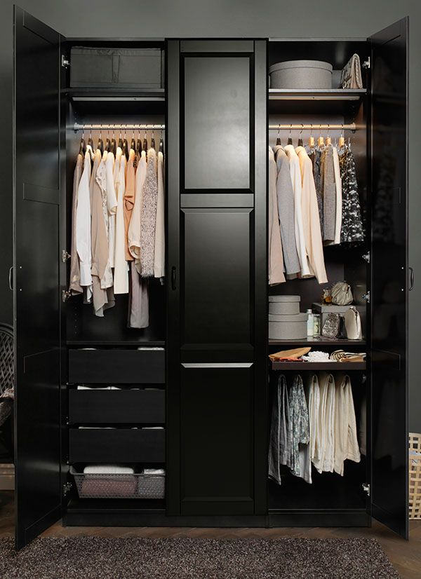A Black Brown Wardrobe Filled With Clothes In Light Pastel Colours