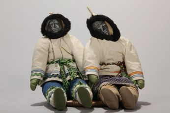 AV.1990.681	 attributed to Kutchaka Louisa Qijuaruq (Amiillak)	 Inukjuak man and woman stuffed dolls sitting with one arm around the other on a round woven lime grass mat. 24 x 28 x 26 cm  © Avataq Cultural Institute