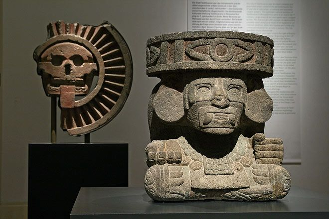 """""""In the foreground:  Huehuetéotl-Tlaloc  Tenochtitlan (Mexico-City), Templo Mayor  1325 - 1521 (?)  Stone  66 x 57,3 x 56 cm  Museo del Templo Mayor, Mexico-City    The Mexica, resp. the Aztecs, copied typical forms of expression of Teotihuacan adapting them to their cult, like for example the Old Fire god. In this case, the position of the hands is different, and attributes of the rain god Tlaloc have been added (canine teeth, rings around the eyes)."""""""