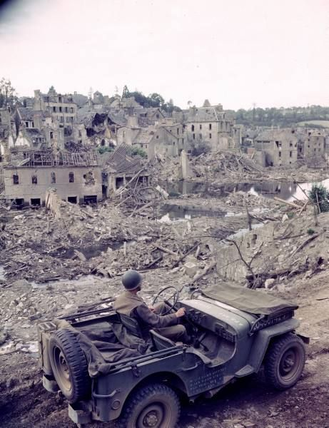 A U.S. Army soldier drives a Willys jeep thrown a bombed out city in France.