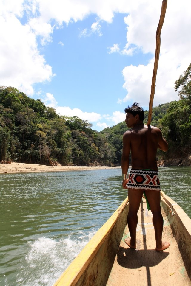 Photographer: Nikki Odderstol  Title: The Embera    Taken in March of 2011. We visited one of the few remaining indigenous tribes of the Embera in Panama. To prove their manhood, young men must master the art of canoeing; part of that entails taking tourists into the jungle using canoes. Today it had just rained, so they could easily maneuver through the river.. The young man is looking the the left in search of crocodiles to ensure that none approach the canoes.
