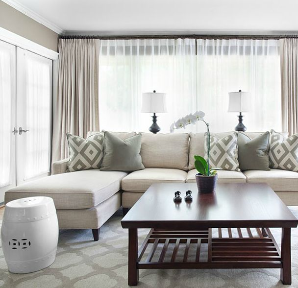 source: Mark Williams Design Gorgeous monochromatic living room design with gray walls paint color, ivory Mitchell Gold + Bob Williams Charlotte sofa with chaise lounge, David Hicks La Fiorentina pillows, gray pillows, white garden stool, Room & Board Shinto square cherry square table, blue lamps, oatmeal linen window panels curtains, and quatrefoil patterned rug in mist.
