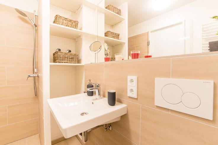 Einrichtungsidee Badezimmer: Warme Farben mit roten Akzenten, Badmöbel in cremeweiß, großer Spiegel im Hintergrund. Apartment in Hamburg.