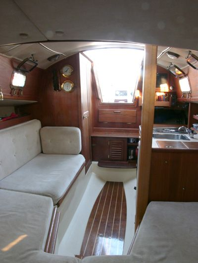 """Pacific Seacraft Flicka 20 """"Caraway"""" - Interior (Aft View). Notice the settee on the starboard side and the galley on the port side. All the way aft is the companionway, which is the entrance to the cabin. Next to the companionway ladder on the starboard side is the enclosed head."""