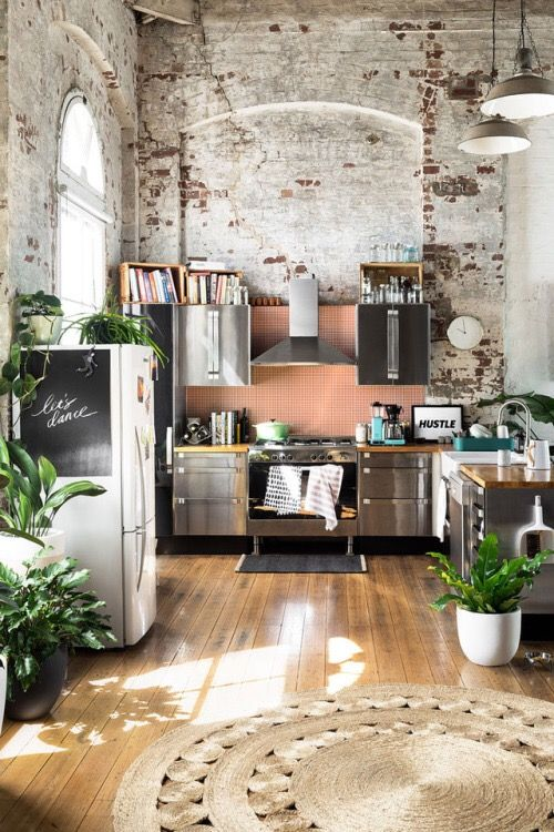 Murs bruts et peinture rose saumon se rencontrent dans la cuisine aux meubles métallisés
