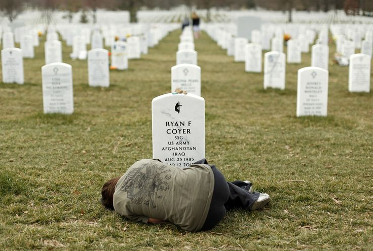 Lesleigh Coyer, 25, of Saginaw, Michigan, lies down in front of the grave of her brother, Ryan Coyer, who served with the U.S. Army in both Iraq and Afghanistan.
