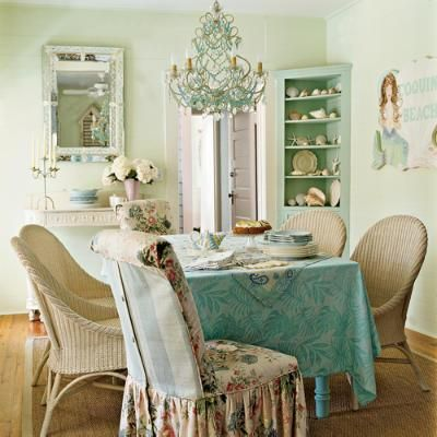 Cute cottage shabby dining room with crystal chandelier aqua blue corner shelf turquoise table cloth wicker chairs and floral fabric covered chair.