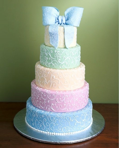 Chic, modern, elegant, stylish wedding cake featuring a large bow and classic tiers in palette of pastel colors - blue, pink, yellow, green and ivory.