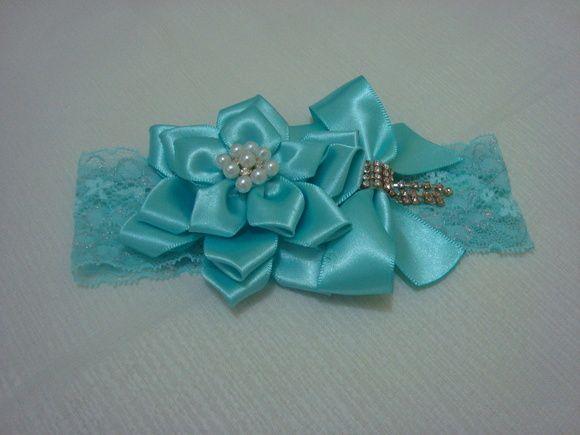 faixa em renda elastano com flor em fita cetim com botão em pérolas e strass e lindo laço com strass. R$ 14,90