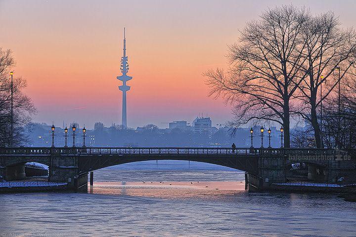 Aussicht auf die Schwanenwik-brücke an der Alster in Hamburg nach Sonnenuntergang im Winter. Auf der Brücke steht eine einzelne Person die in den pastellfarben rötlichen Himmel schaut vor dem sich die Silhouette des Heinrich Hertz Fernsehturm abzeichnet.