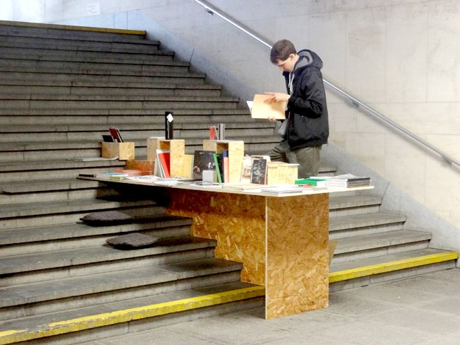 RELEVANCE: using the surroundings to catch peoples attention CONCEPT: a book shelf on stairs to stop people to stop and read. good way to stop people, catch their attention STYLE: simple made from ply board. looks like a temporary thing thats someone just quickly made.