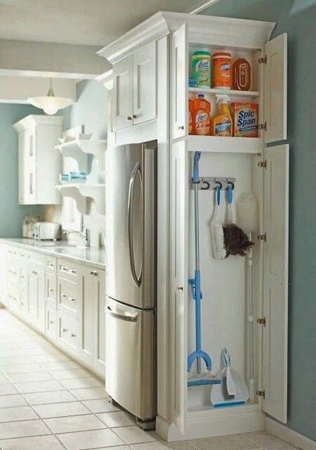 Broom/vacuum closet, floor to ceiling flush with refrigerator in front.  Cabinets above refrigerator with pull out inserts.