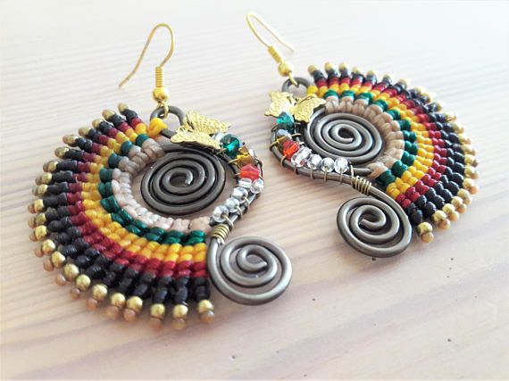 Welcome to Bohemian Style Thai Earrings...  You're looking at a unique pair of reggae themed fire colour macrame earrings, woven around dark wire, designed as dangle/drop earrings for pierced ears. The earrings feature a gold brass butterfly motif and complimentary glass beads.      www.bohemianstyleshop.etsy.com