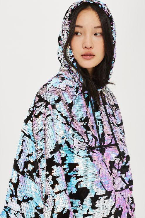nvest in your latest festival piece with this statement poncho with all over iridescent sequin detail. In a blue mix colour way, it comes with a practical hood for when unexpected weather hits