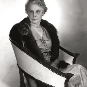 Vogue's editor-in-chief Edna Woolman Chase sits in leather arm chair wearing a mink collar over a metallic cloqu? dress with a single strand of pearls, pearl stud earrings, and a brooch; Photo caption recognizes Mrs. Chase's recent honor as a Chevalier of the Legion of Honor by the French Government