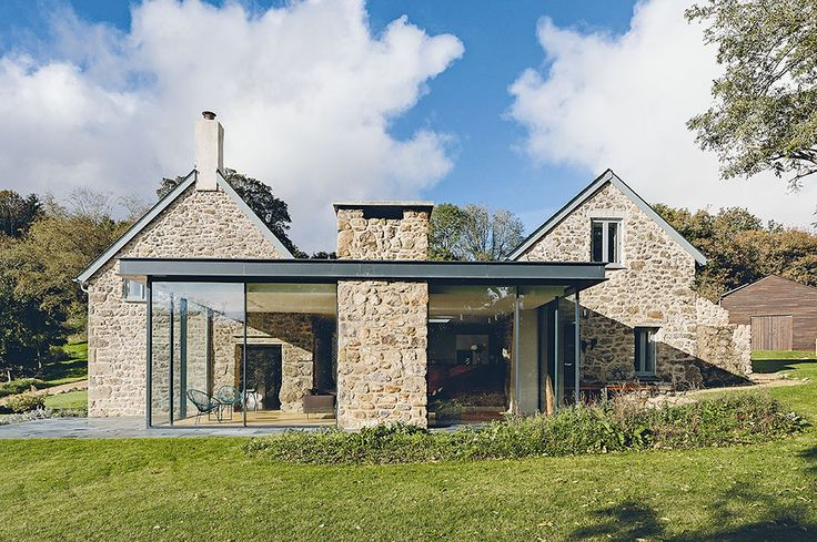 Single storey steel framed glass extension to a traditional stone cottage