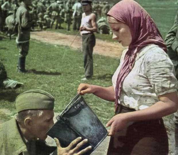 Una mujer ucraniana le da agua a un soldado soviético capturado. [1941]
