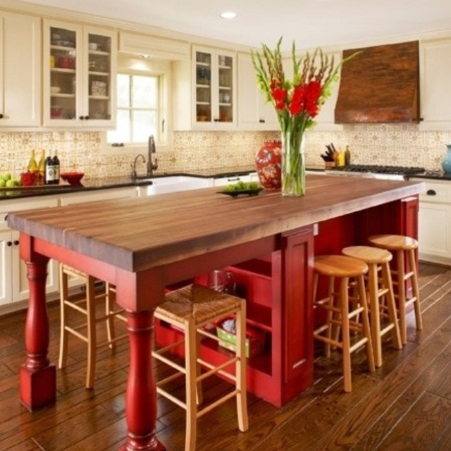 Red island with butcher block top. White cabinets with black counters