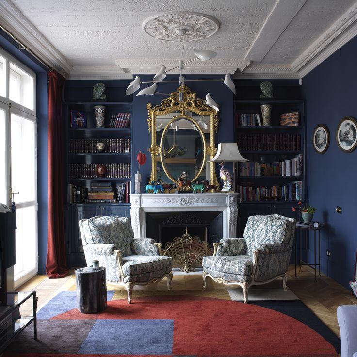 """Все вещи в гостиной — """"иностранцы"""". Потолочный светильник по дизайну Дэвида Уикса и стол-пенек куплены в Нью‑Йорке, итальянская лампа 1950‑х годов с основанием в виде павлина привезена из Ниццы, каминный портал с зеркалом XIX века и кресла 1930-х годов найдены на блошином рынке в Париже, дизайнерский ковер происходит из антверпенской галереи N. Vrouyr."""