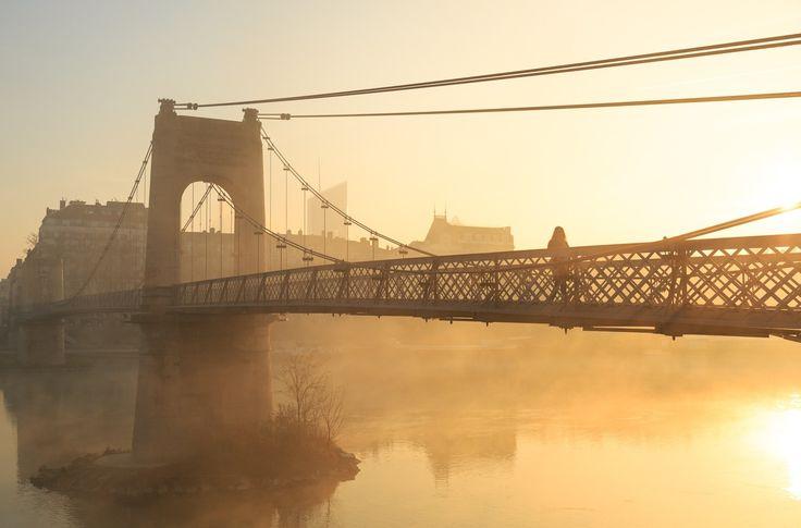 Passerelle du Solei - A girl walking on the monumental 'Passerelle du College' footbridge over the Rhone river in Lyon during a foggy, autumn sunrise. Good morning sunshine!