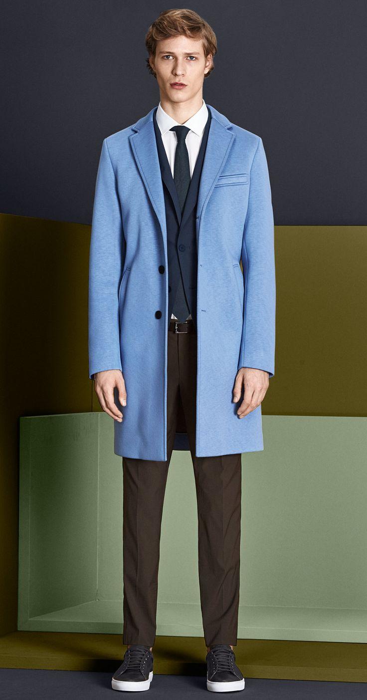 Pastelblauwe mantel, donkerblauwe jas, wit overhemd, broek in donker naturel met een donkerblauwe stropdas, groene ceintuur en schoenen van BOSS