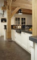 Prachtig voorbeeld van een landelijke keuken. Zwart witte keuken met oude houten balken en een houten plafond.