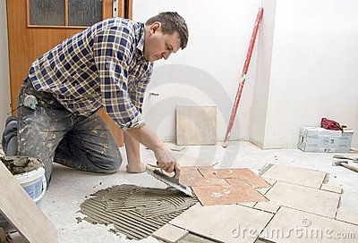 A construction worker putting on new floor tiles.  <a…