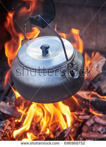 Stock Photo: Metallic coffee pot in campfire heat while trekking. Wood burning with flames beneath the pot. -