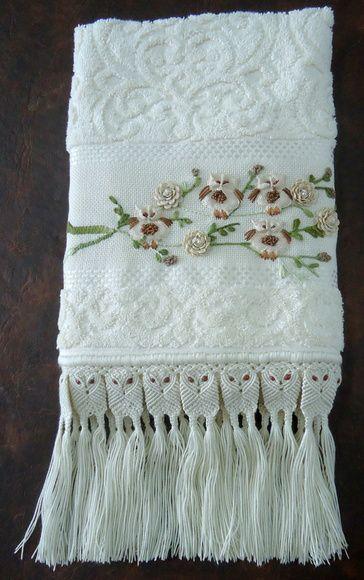 Toalha de rosto finamente bordada com sianinha e fita, motivo de coruja e acabamento em macramê. Na cor bege. R$ 70,00
