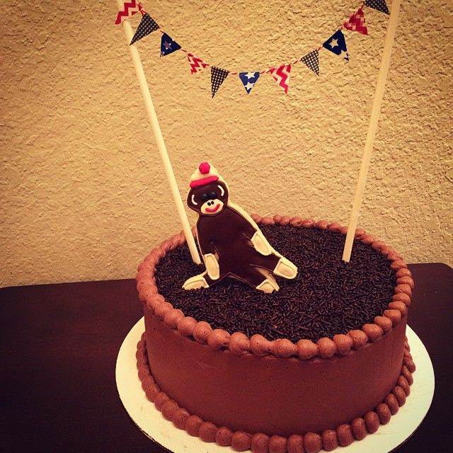 Sock monkey baby shower cake! A strawberry cake with chocolate buttercream frosting, a sock monkey cookie and a banner across the top!