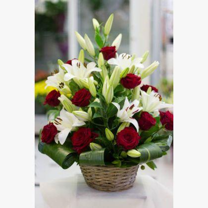 Ανθοσύνθεση σε καλάθι με κόκκινα τριαντάφυλλα, λευκά λίλιουμ και πρασινάδα.