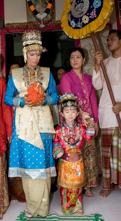 A modern-day Chitty bride and her entourage, all wearing Malay dress. The bride is also wearing a Baba-Nyonya headdress.