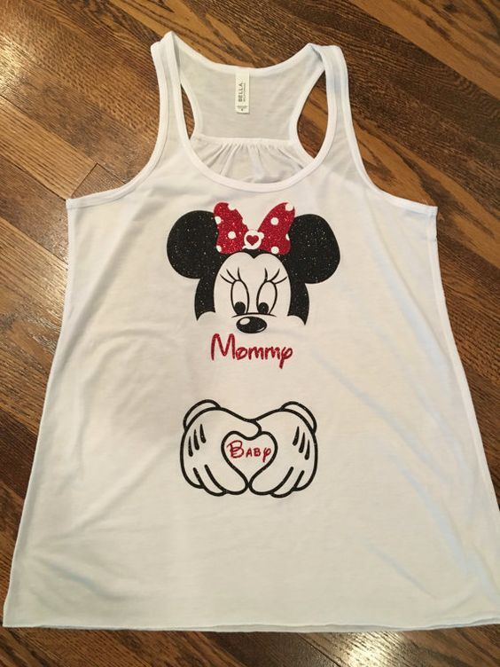 Womens Minnie Mouse and Baby Tank! Perfect for baby announcements, Minnie Mouse Maternity. If you your pregnant you can still go to Disney in style with this tank. Heat transfer high quality glitter can be made in any color. Tank top: flowy racerback tank top. 65% polyester, 35% viscose.  Also can be made in matching child onsie or shirt without the baby and hands!  All orders are custom made to order with no returns.  For guaranteed 7 day delivery please add the rush your item in our shop…