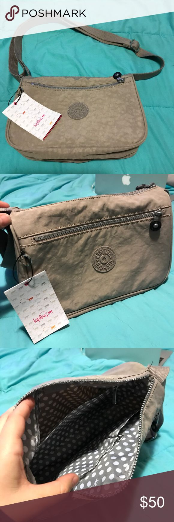 Kipling Callie in Dune Beige BNWT small messenger Brand new Kipling side bag with tags still attached. Light grey small messenger bag. Adjustable strap and tons of pockets. Perfect everyday bag. About 13 inches across. Never been used. Kipling bag in sand / beige Kipling Bags Crossbody Bags