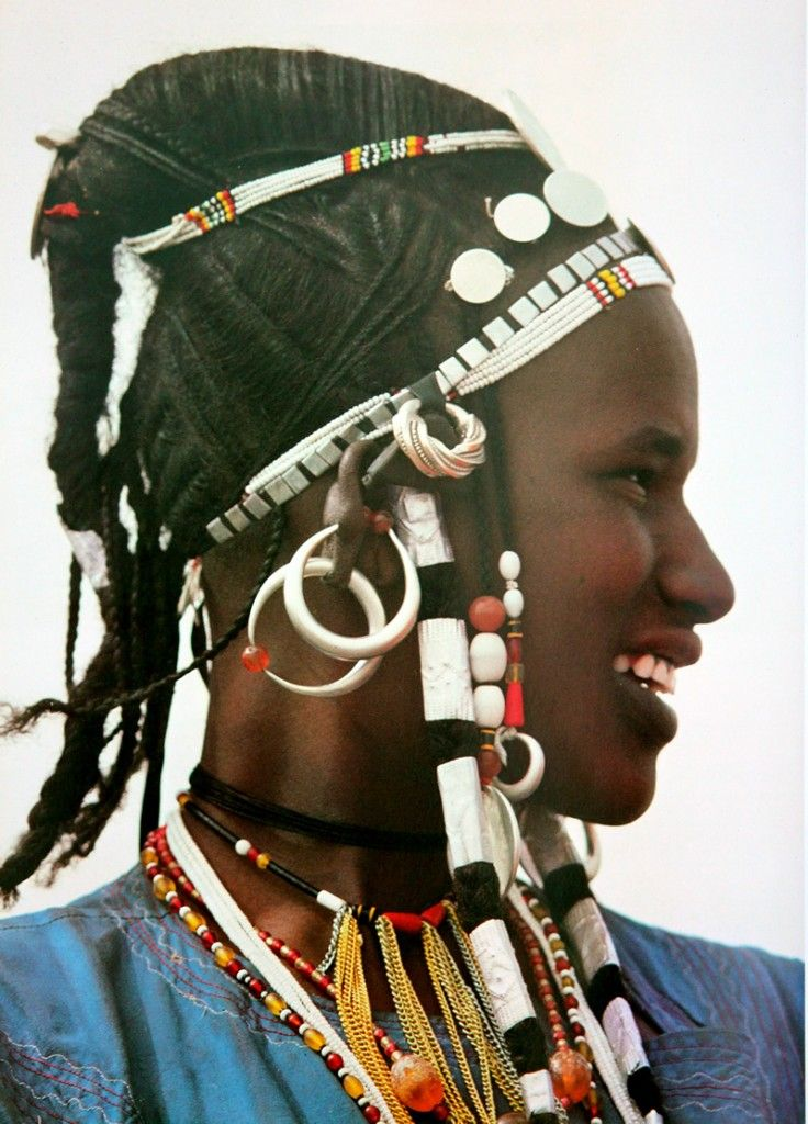 "Africa | ""Maria Teresa dollars from Austria and French Franc pieces, originally imported into Africa as currency, have been widely used across the savannah as hair decoration. The Fulani of northern Upper Volta have crest-like hairstyles, sometimes padded with a piece of cloth inside, which they decorate with these coins .. the hair rings and silver bands wrapped around their plaits are all made of the same melted down coinage"" 
