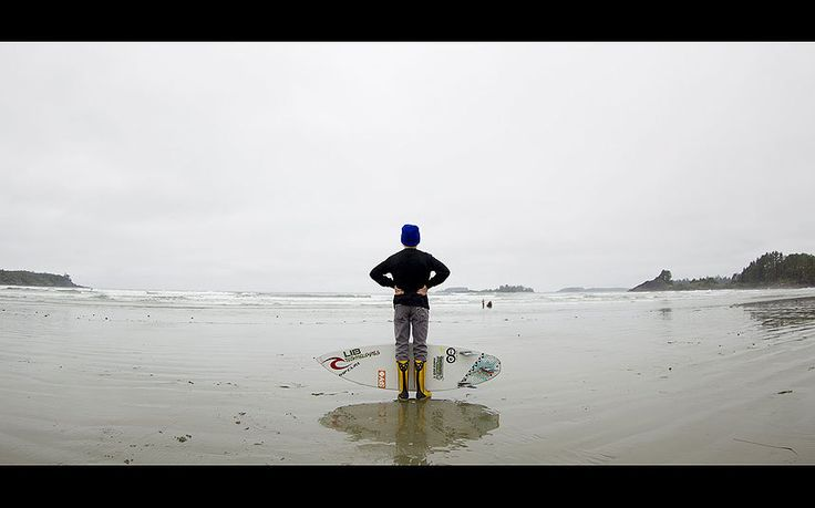 Reed Platenious holds surfer Ben Murphy's board during the Canadian Surf Championship in Tofino, British Columbia May 31, 2015.