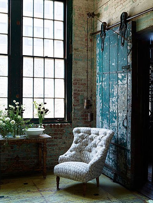 Teal paint on a barn door. Old brick walls. Tall ceiling. Black framed windows.