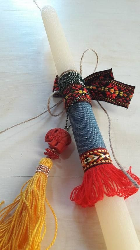 Aromatic candle and a special gift for fashionable girls. An ethnic pendant with metallic chain, a red elephant and a rich yellow tassel.