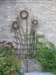 daisy-looking flower toppers on twig trellis