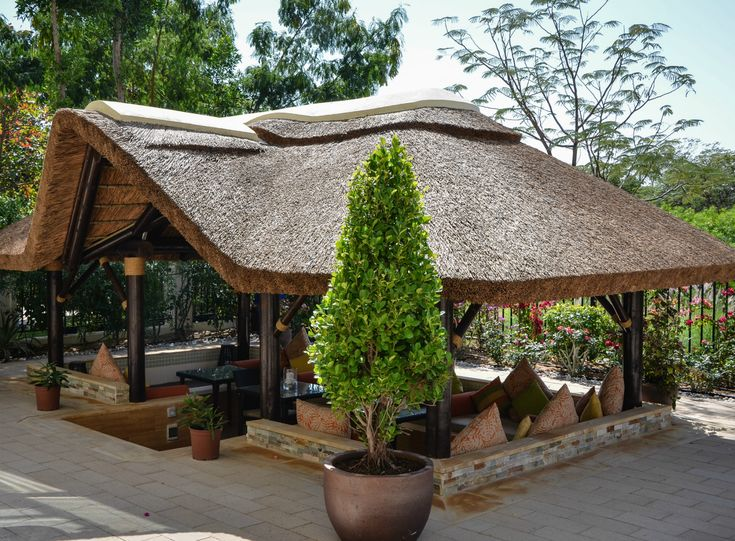 Outdoor thatched gazebo with seating, perfect for al fresco outdoor dining!