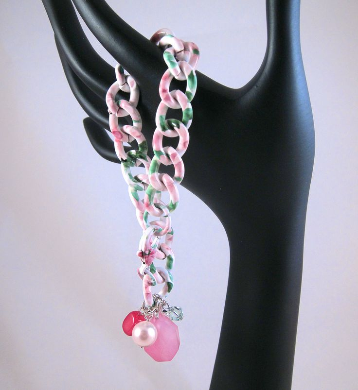 Floral print chain gives the bracelet an interesting and appealing, whimsical look. Very girly even with the chunky chain.   The pastel floral print chain is reminiscent of a watercolor painting in white with soft pink flowers and green leaves. The pastel colors make it the perfect fit for springtime. The charm dangles include a pretty silver heart shaped filigree key, 2 pink chalcedony semi precious stones, a soft pink colored Swarovski pearl and a mint green Swarovski crystal.