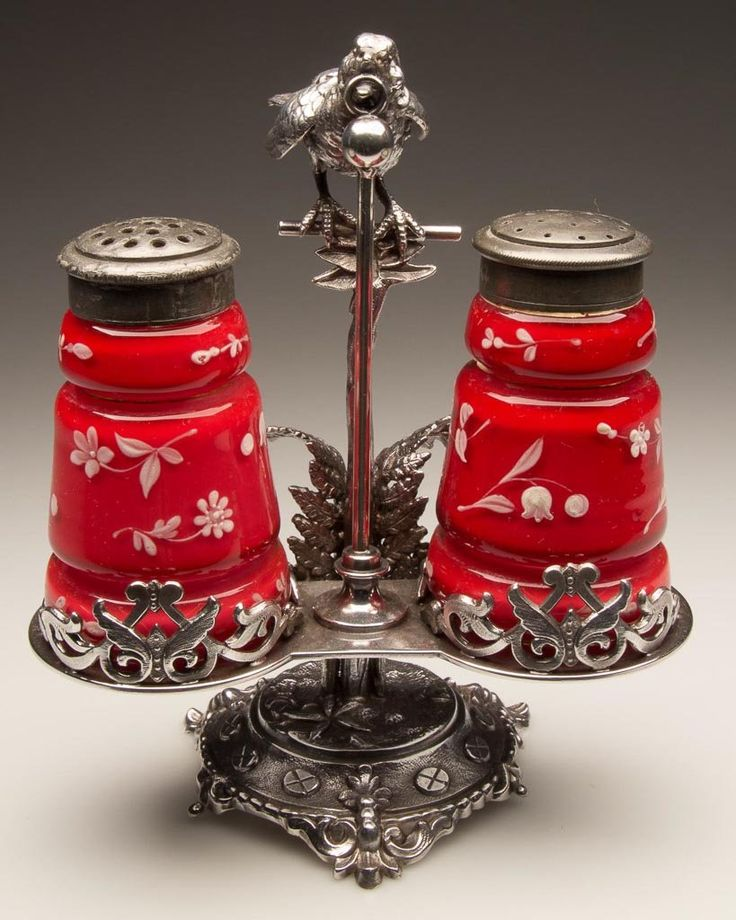 DOUBLE CREASED PAIR OF SALT AND PEPPER SHAKERS, opal cased red with white enamel decorations, matching period two-part lids. Fitted in a figural Bird and Ring quadruple-plate stand marked for the Meriden Britannia Co. and numbered 50. Fourth quarter 19th century.