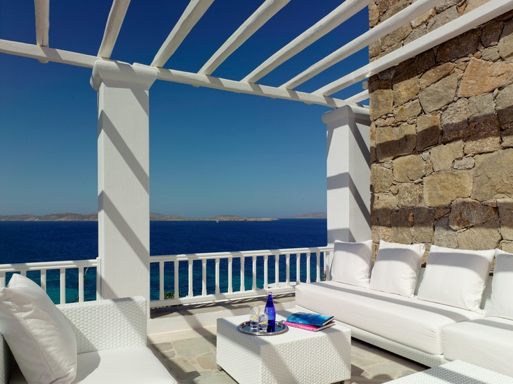 White Bar Pergola of the Mykonos Grand Luxury Hotel & Resort: dramatic outdoor terrace with a telescope to observe views of the Aegean Sea