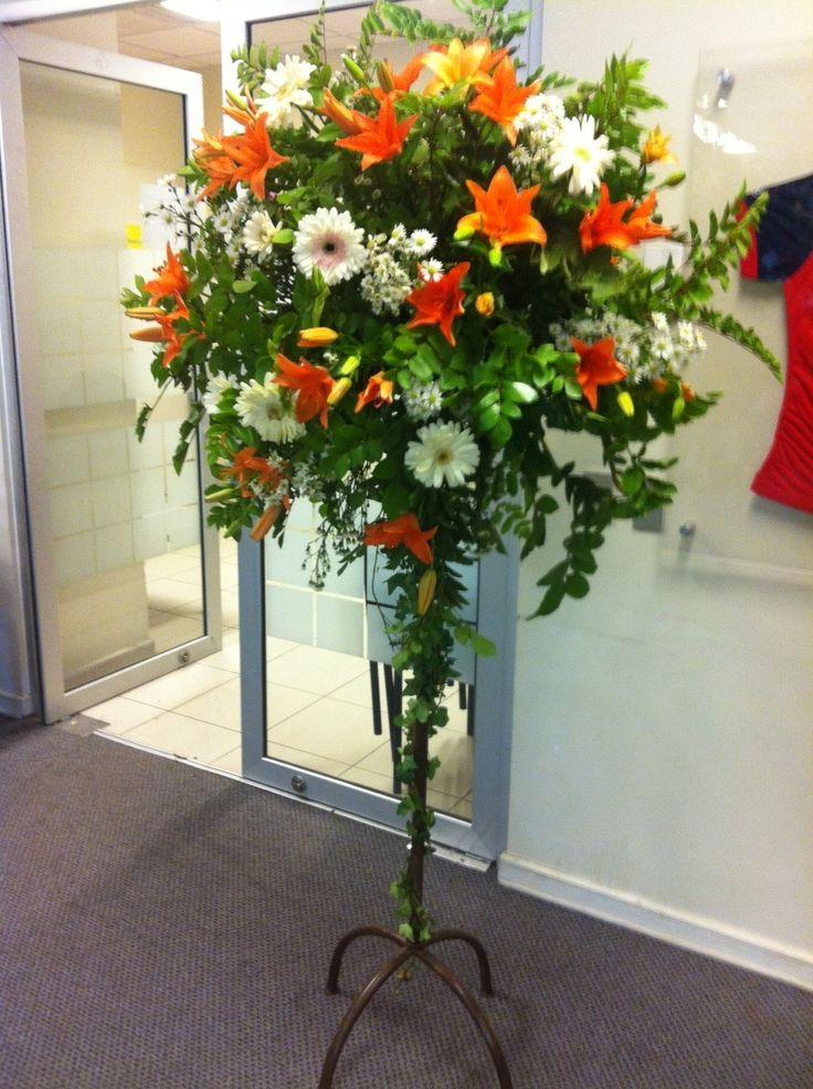 Pedestal para evento con gerberas, lilium, flores secundarias con follajes varios.