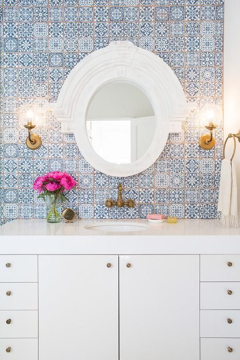 White and blue bathroom features a wall clad in blue Moroccan tiles, Fez Blue Vintage Moroccan Victorian Encaustic Effect Pattern Wall & Floor Tiles, lined with a white lacquered washstand adorned with aged brass knobs topped with thick white quartz and paired with an aged brass faucet placed under a white Mansard mirror.