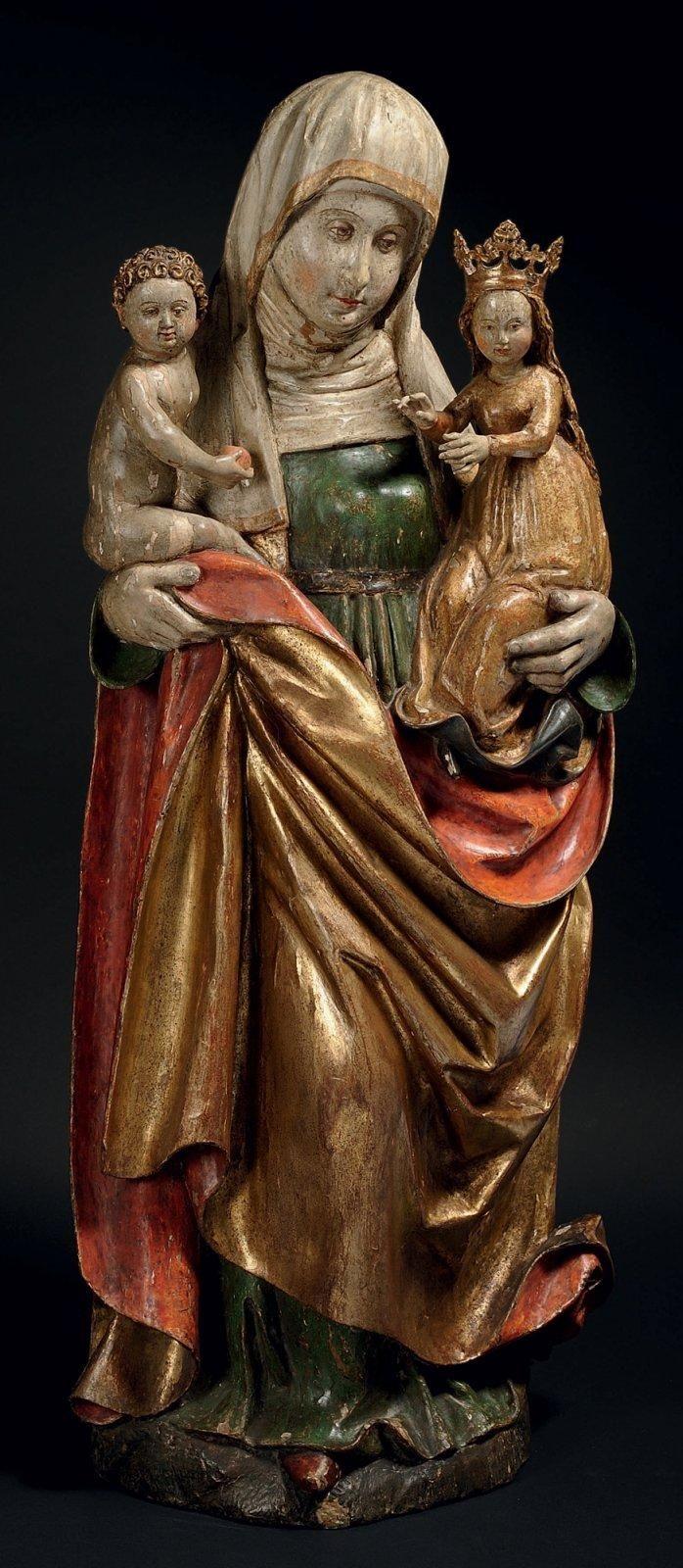 SAINTE ANNE TRINITAIRE en tilleul sculpté, doré et polychromé. Dos creusé. La sainte est debout portant la Vierge sur son bras droit et Jésus sur l'autre; visage encadré d'une guimpe et d'un voile; elle est vêtue d'une robe ceinturée et d'un manteau dont un pan revient sur le devant; tête de la Vierge ceinte d'une haute couronne fleuronnée posée sur la chevelure tombant largement dans le dos; le Christ est nu tenant un fruit dans sa main droite. Allemagne du sud, vers 1520