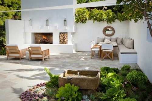 CONCRETE EVERYTHING. How easy to clean this must be... Even the fountain looks like a stained/acid-washed concrete, surrounded by succulents. The white concrete bench seating allows you to swap out colored cushions seasonally, and the plants cascading down the concrete walls are beautiful with their green-on-white contrast. The fireplace and wood holder bring in the fire/earth feel, grounding the entire area.