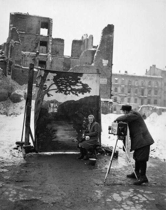 A photographer uses his own backdrop to mask Poland's World War II ruins while shooting a portrait in Warsaw, November 1946 -