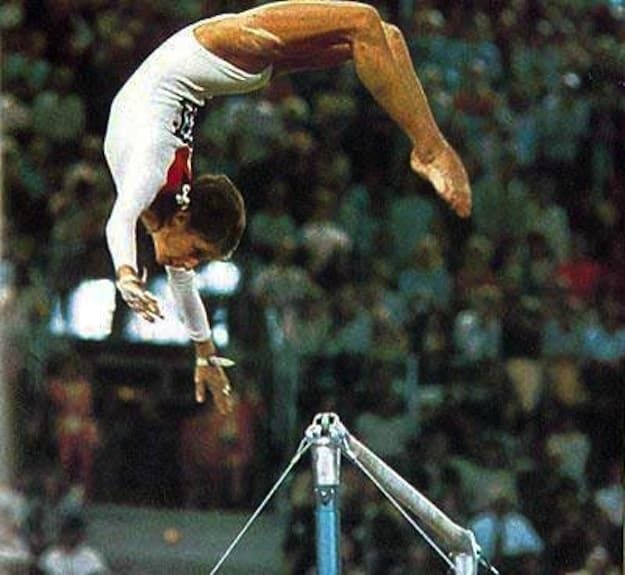 The manuever on the uneven bars is when a gymnast, from a stand on the high bar, performs a back flip on the lower bar and then regrasps the high bar.